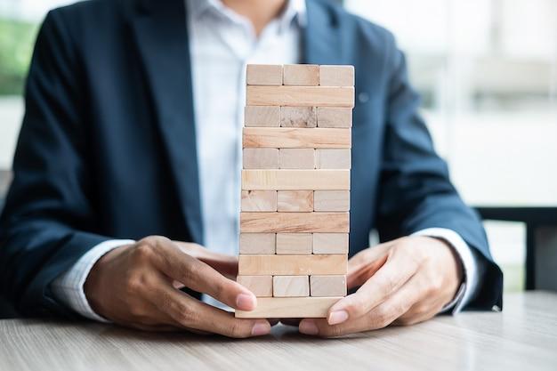 Mão de empresário segurando o bloco de madeira na torre