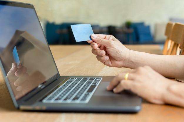 Mão de empresário segurando o cartão de crédito e usando o laptop na mesa de madeira.