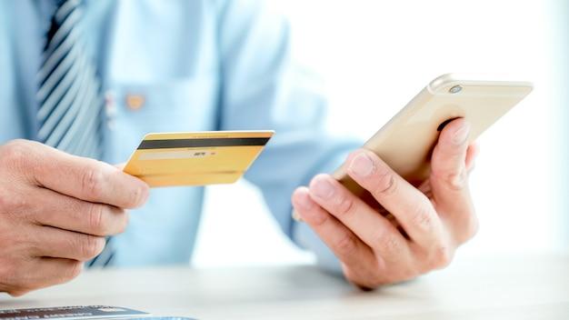 Mão de empresário segurando o cartão de crédito e usar o smartphone para fazer compras online em casa, pagamento de comércio eletrônico, internet banking, gastar dinheiro para as próximas férias.