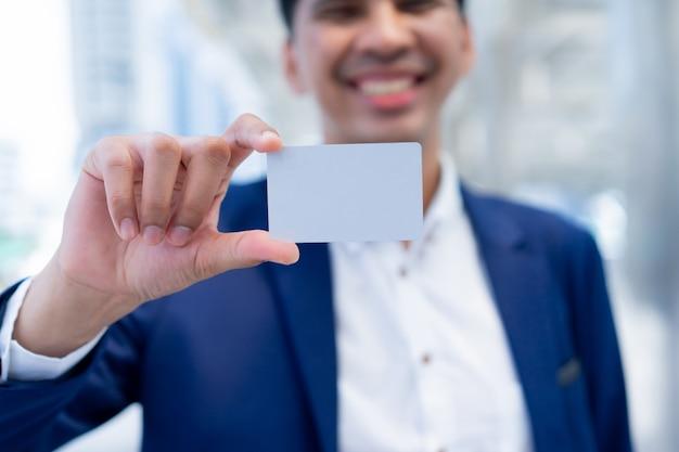 Mão de empresário segurando o cartão de crédito em branco branco