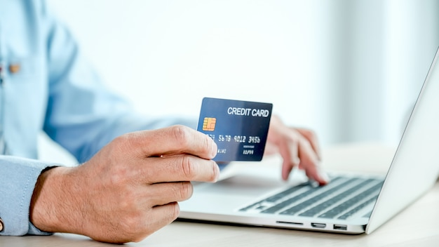 Mão de empresário segurando o cartão de crédito para fazer compras online em casa.