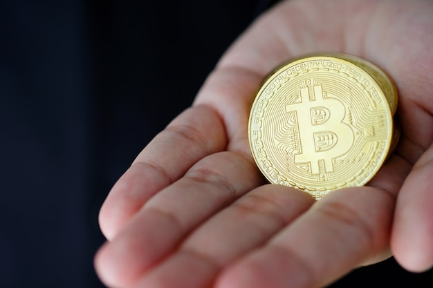 Mão de empresário segurando o conceito de bitcoins, cryptocurrency e blockchain