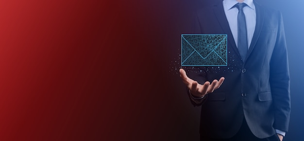 Mão de empresário segurando o ícone de carta, ícones de e-mail. entre em contato conosco por e-mail de boletim informativo e proteja suas informações pessoais de mensagens de spam. central de atendimento ao cliente, entre em contato conosco. boletim informativo de marketing por e-mail.