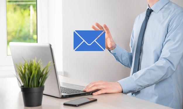 Mão de empresário segurando o ícone de e-mail, entre em contato conosco por e-mail de boletim informativo e proteja suas informações pessoais de mensagens de spam. centro de atendimento ao cliente entre em contato conosco conceito