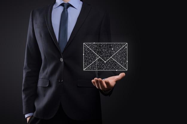 Mão de empresário segurando o ícone de e-mail, entre em contato conosco por e-mail de newsletter e proteja suas informações pessoais de mensagens de spam. centro de atendimento ao cliente entre em contato conosco conceito.