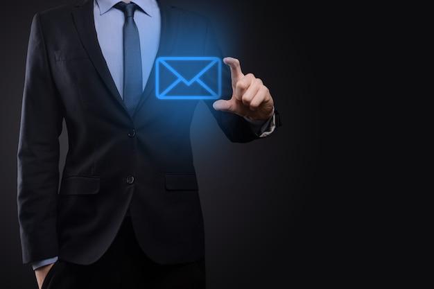 Mão de empresário segurando o ícone de e-mail, entre em contato conosco por e-mail de newsletter e proteja suas informações pessoais de mensagens de spam. centro de atendimento ao cliente entre em contato conosco conceito