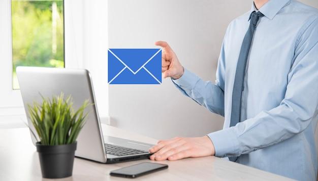 Mão de empresário segurando o ícone de e-mail, entre em contato conosco por e-mail de newsletter e proteja suas informações pessoais de mensagens de spam centro de atendimento ao cliente entre em contato conosco conceito