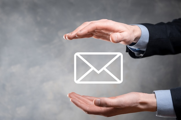 Mão de empresário segurando o símbolo do e-mail, entre em contato conosco por e-mail de newsletter e proteja suas informações pessoais contra spam. centro de atendimento ao cliente entre em contato conosco conceito.