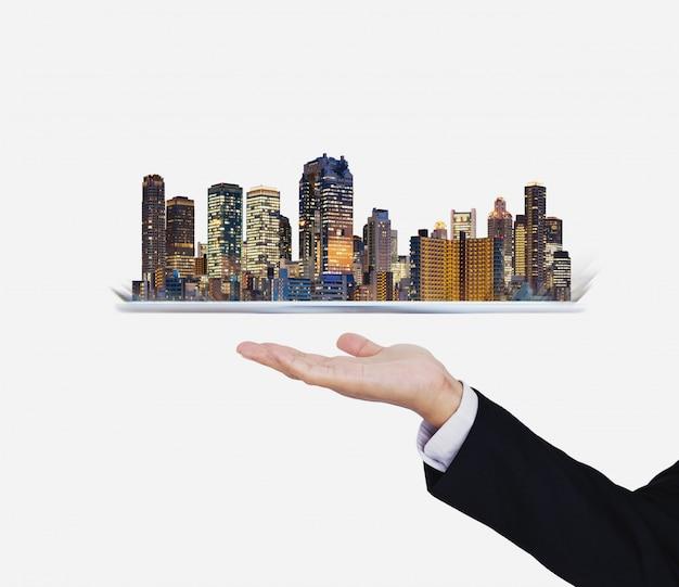 Mão de empresário segurando o tablet digital com holograma moderno edifício