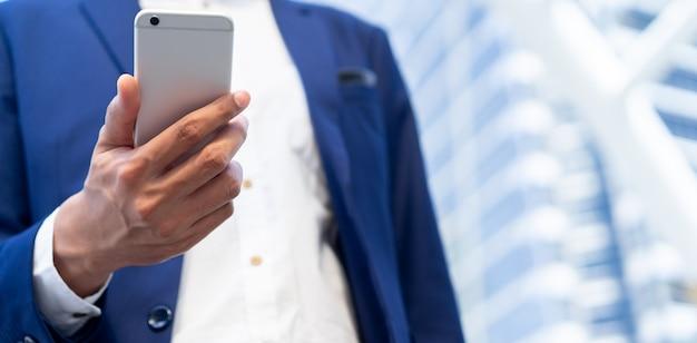 Mão de empresário, segurando o telefone inteligente (dispositivo móvel) para verificar as notícias de negócios no site