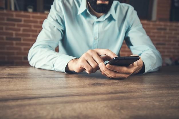 Mão de empresário segurando o telefone inteligente na mesa