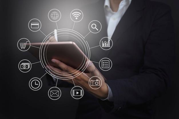 Mão de empresário segurando pagamentos de tablet em compras online com rede de clientes de ícones gráficos