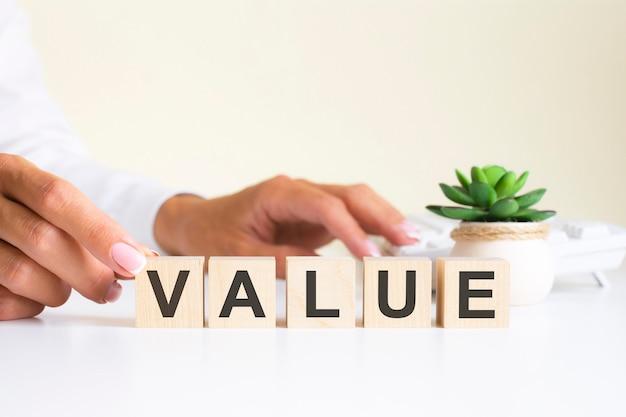Mão de empresário segurando um bloco de cubos de madeira com palavra de negócios de valor no fundo da mesa. conceito de missão, visão e valores centrais.