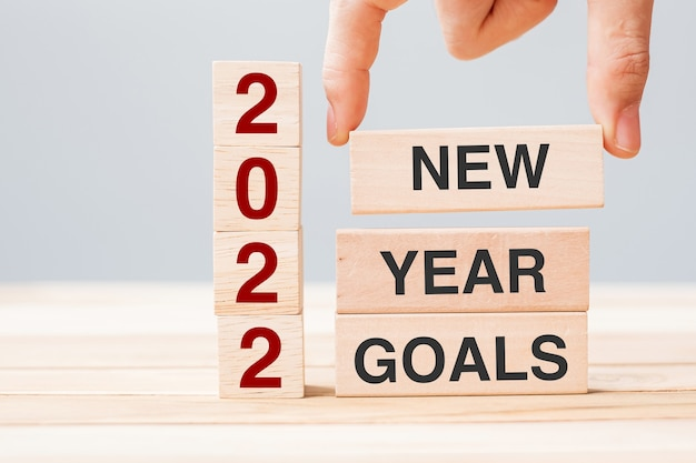 Mão de empresário segurando um bloco de madeira com texto 2022 objetivos de ano novo no fundo da mesa. conceitos de resolução, estratégia, solução, negócios e férias