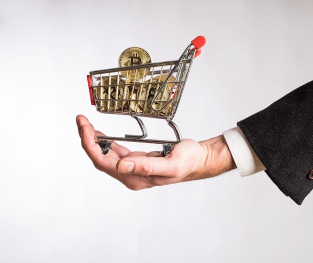 Mão de empresário segurando um carrinho de compras cheio de bitcoins