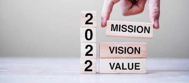 Mão de empresário segurando um cubo de madeira com o texto 2022 missão, visão e valor no fundo da mesa. conceitos de resolução, estratégia, solução, objetivo, negócios e feriado de ano novo