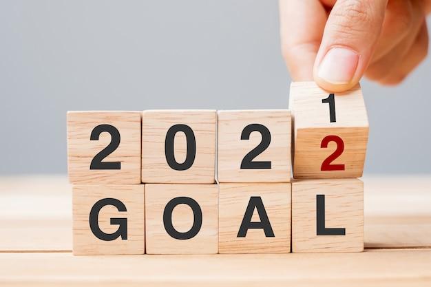 Mão de empresário segurando um cubo de madeira e virar o bloco 2021-2022 objetivo no fundo da mesa. resolução, plano, revisão, mudança, conceitos de feriado de ano novo e início