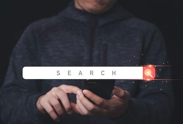 Mão de empresário segurando um telefone celular e um design digital de um ícone de barra de busca
