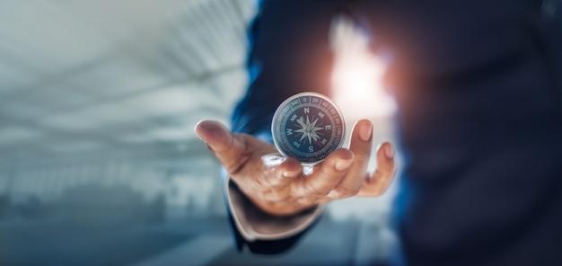 Mão de empresário segurando uma bússola navegando no mercado financeiro e de pesquisa e desenvolvimento