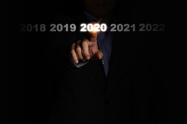 Mão de empresário tocando 2020 ano em fundo preto. é o símbolo da mudança fiscal e do ano comercial.