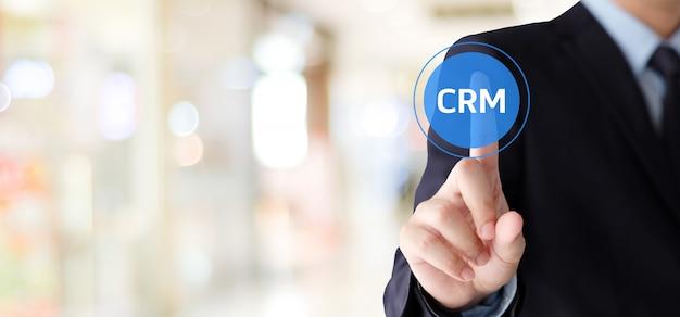 Mão de empresário toque crm, gestão de relacionamento com cliente, ícone sobre fundo de desfoque