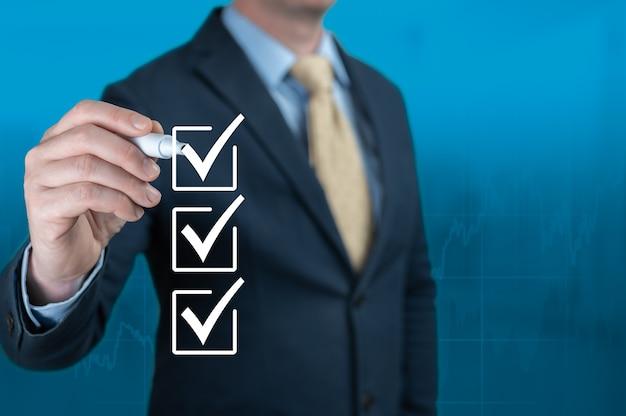 Mão de empresário, verificando as caixas da lista de verificação sobre fundo azul. empresário com caixas de seleção de caneta