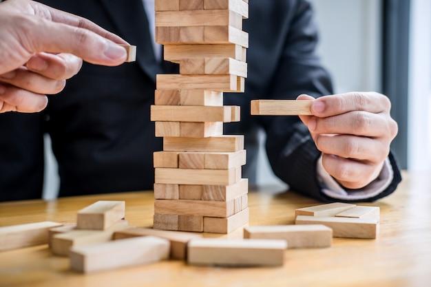 Mão de empresários colocando e puxando o bloco de madeira na torre