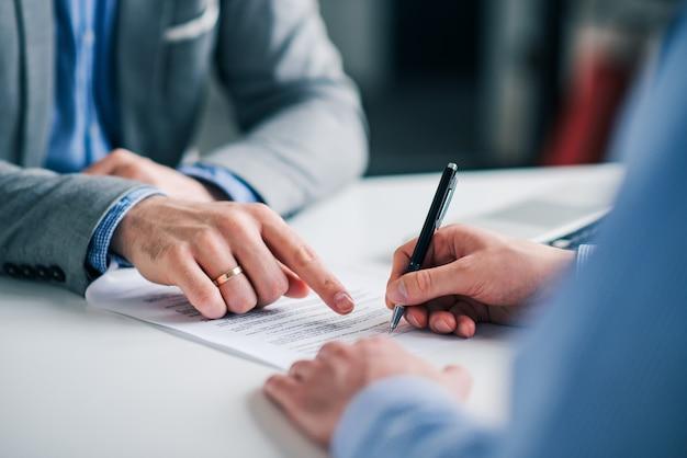 Mão de empresários está apontando onde assinar um contrato, documentos legais ou formulário de candidatura.