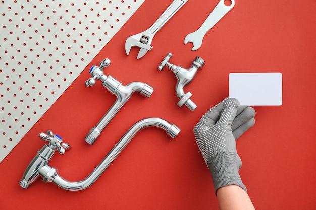 Mão de encanador com cartão de visita e itens