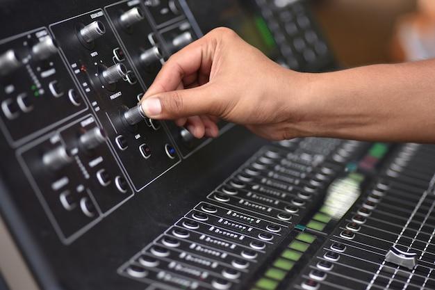 Mão de engenheiro de som que ajusta o nível de ajuste do teste de som na mixagem de áudio