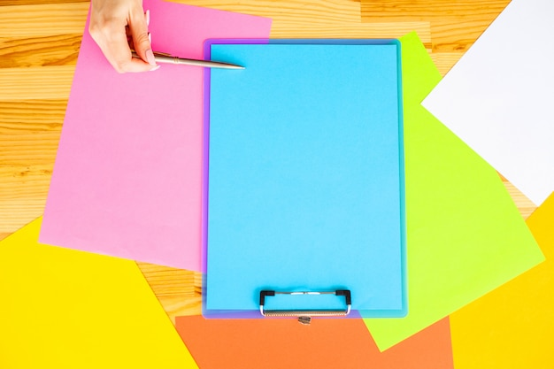 Mão de escritório, segurando uma pasta com um papel de cor azul e caneta