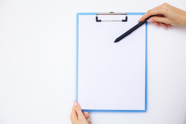 Mão de escritório segurando uma pasta com um papel de cor branca no fundo da mesa branca. copyspace.