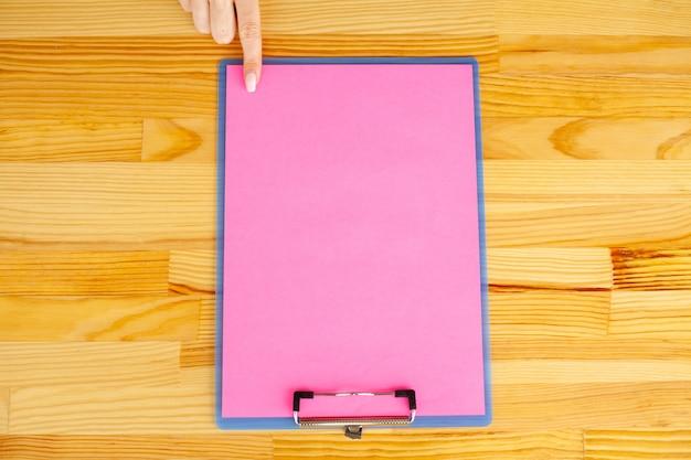 Mão de escritório, segurando uma pasta com um papel de cor rosa