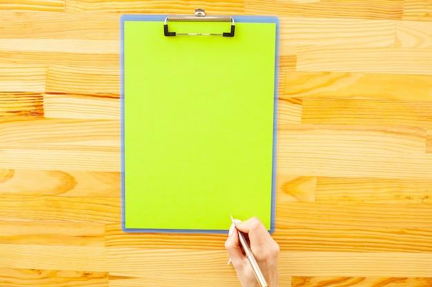 Mão de escritório, segurando uma pasta com um papel de cor verde e caneta