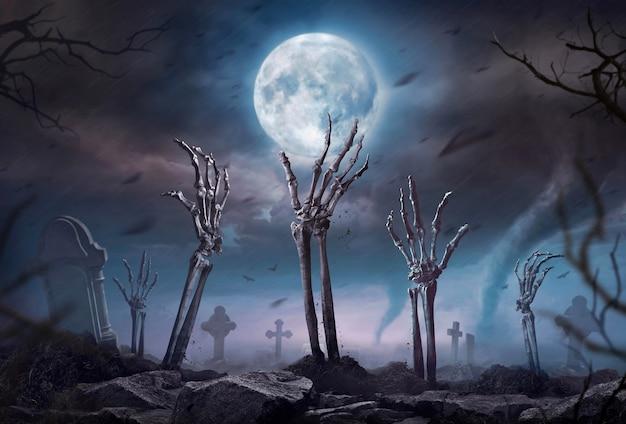 Mão de esqueleto de zumbi subindo na noite escura de halloween.
