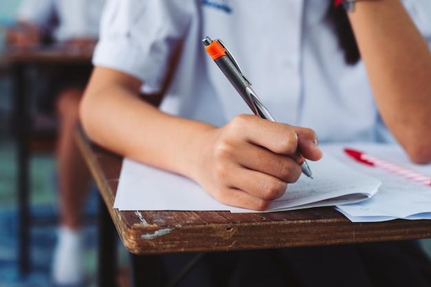 Mão, de, estudante, pena segurando, e, fazendo exame exame, em, sala aula, com, tensão