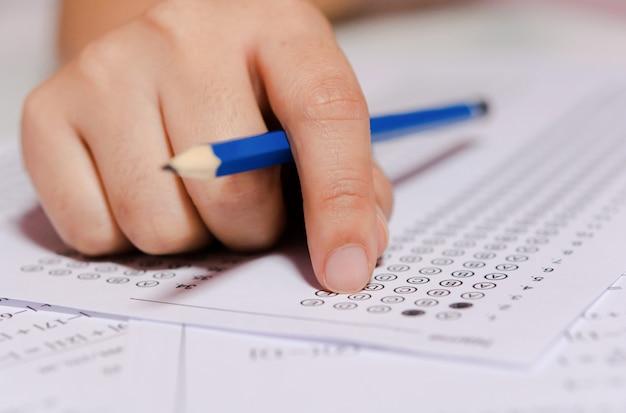 Mão de estudantes segurando a escolha selecionada de escrita a lápis nas folhas de respostas