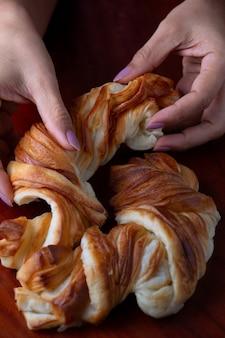 Mão de exibição recortada de mulher separando o pão dinamarquês retorcido