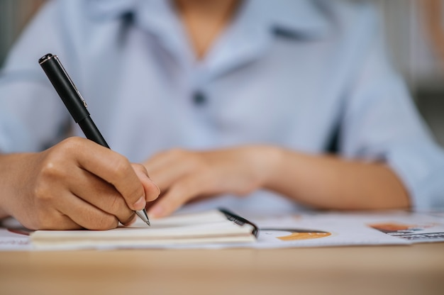 Mão de foco seletivo de jovem asiática em óculos usa caneta trabalhando com papéis no escritório em casa, durante a quarentena covid-19 auto-isolamento em casa, conceito de trabalho em casa