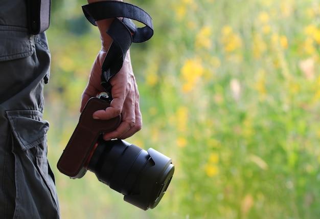 Mão de foco seletivo de um homem com uma câmera digital