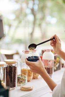Mão de garçom colocando uma colher grande de granulado em uma tigela com sorvete para o cliente