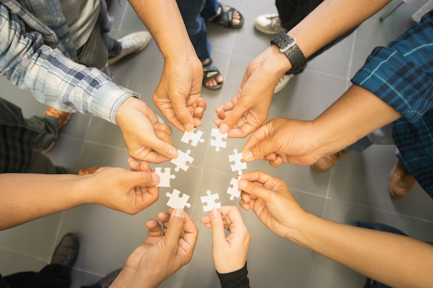 Mão de grupo de trabalho de equipe segurando o quebra-cabeça, conceito trabalhar juntos