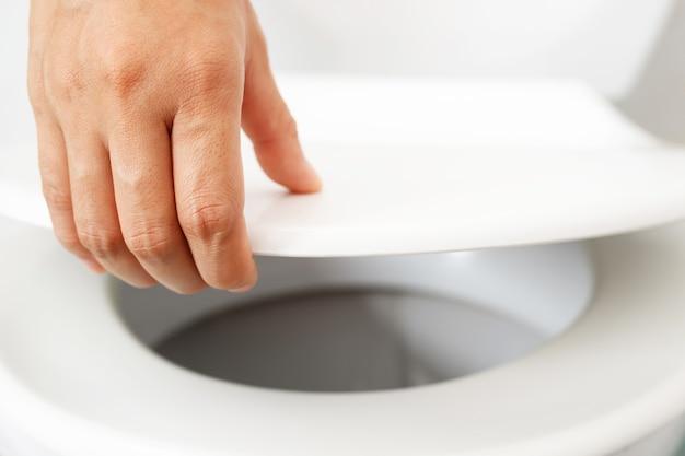 Mão de homem abrindo a tampa do vaso sanitário