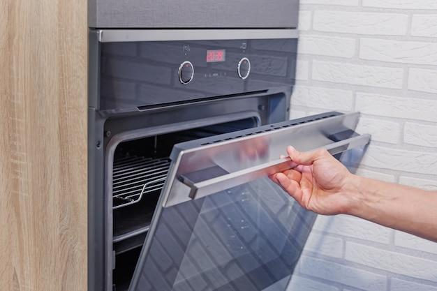 Mão de homem abrir forno elétrico