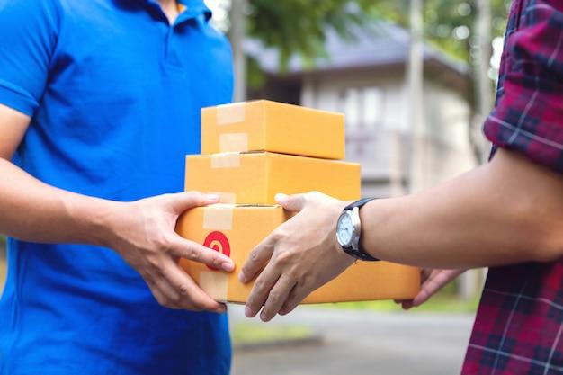 Mão de homem, aceitando uma entrega de caixas de entregador.