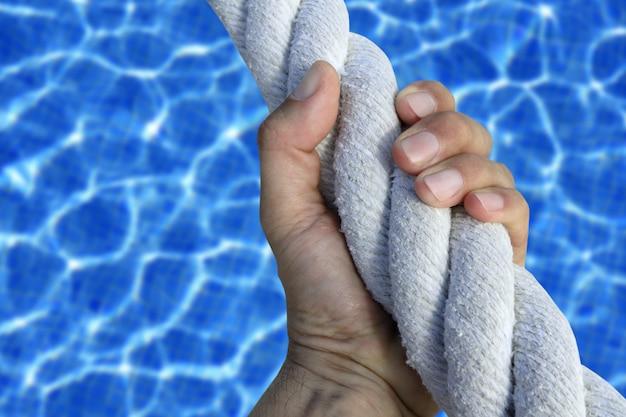 Mão de homem agarrar aperto esporte azul piscina grande corda