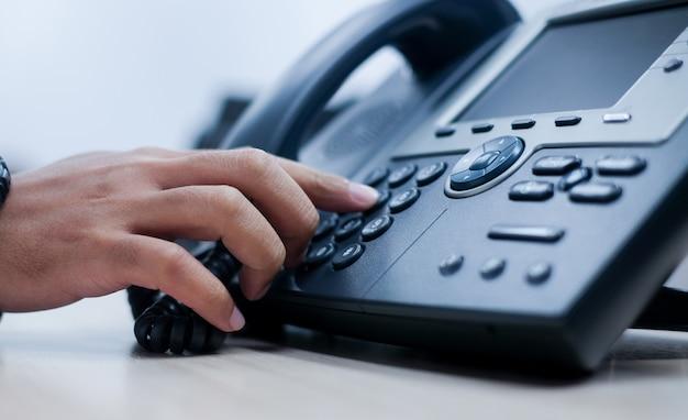 Mão de homem apontar para pressionar o número do botão na mesa de escritório de telefone