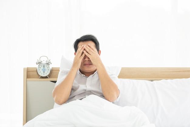 Mão de homem asiático cobrir o rosto enquanto está sentado na cama com o despertador às 6 da manhã.