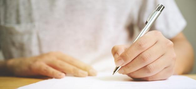 Mão de homem assinando assinatura preenchendo o documento do formulário de candidatura