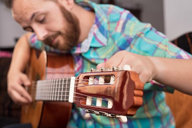 Mão de homem barbudo hipster ajustando o violão.